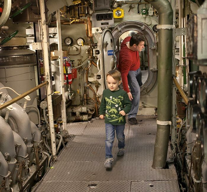 Father and son walking through Submarine Becuna at The Independence Seaport Museum