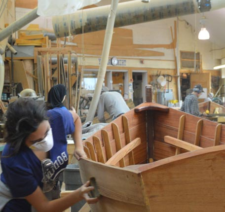 Workers restoring boats at The Independence Seaport Museum
