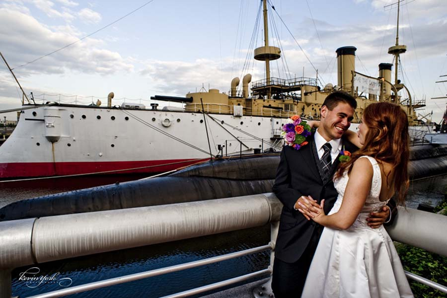 Bride and groom posing for a photo in front of Cruiser Olympia at The Independence Seaport Museum
