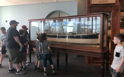 Guests looking at a glass-enclosed model of a ship at The Independence Seaport Museum
