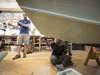 Workers restoring a boat in the ship builders shop at The Independence Seaport Museum