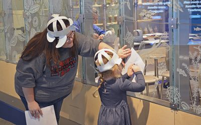 Mother and daughter making rubbings of etched glass at The Independence Seaport Museum
